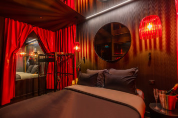 Chambre SM avec une cage, rideau latex rouge